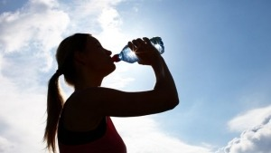 Gegenlichtaufnahme einer Frau, die aus einer Wasserflasche trinkt